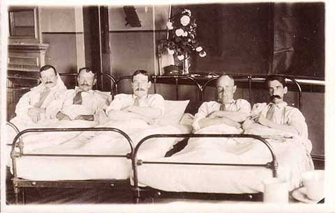 Men in bed postcard